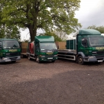 3 green trucks parked in a row saying Premier Loos on the front.