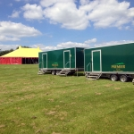 2 green toilet trailers in a field next to a red and yellow tent.