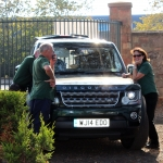 A green Land Rover Discovery with people stood around it.