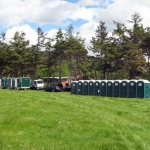 A row of green portaloo cubicles in a field.
