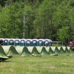 Green tents in a field in front of green portaloo cubicles.