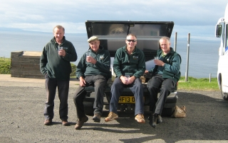 4 men in green jackets sat in the back of a vehicle, holding drinks.