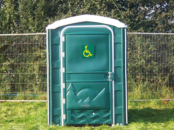 A green portaloo cubicle outside with a disabled sign.