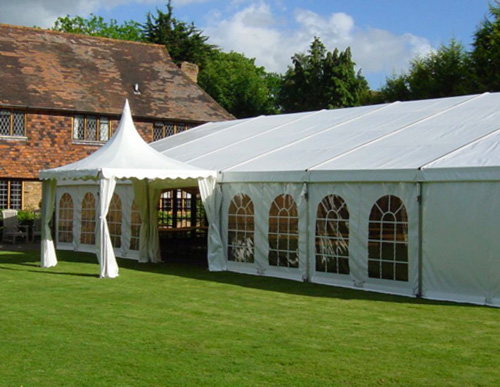 A white marquee outside, next to a red brick house.