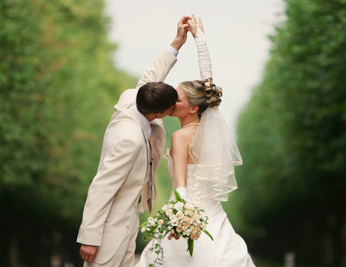 A bride and groom kissing, holding flowers.