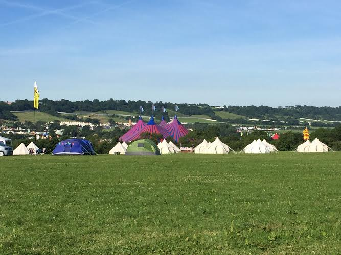 A field with tents in the distance at a festival.