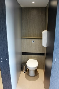 A black and blue cubicle with a toilet.
