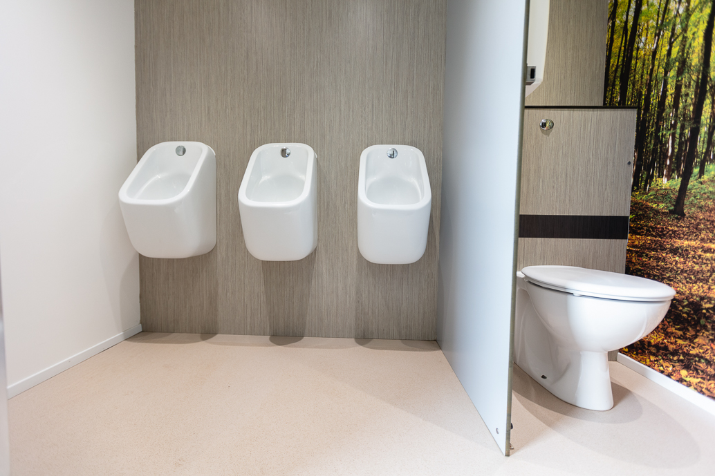 A bathroom with 3 urinals in a row next to a toilet.
