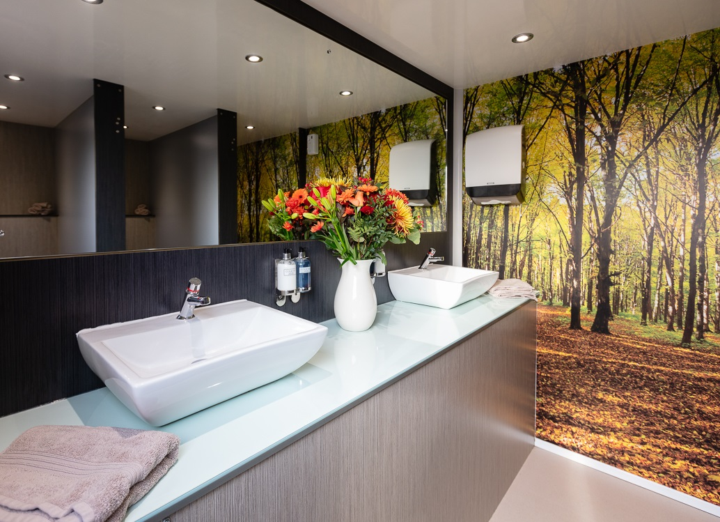 A bathroom with sinks, mirrors and tree wallpaper.